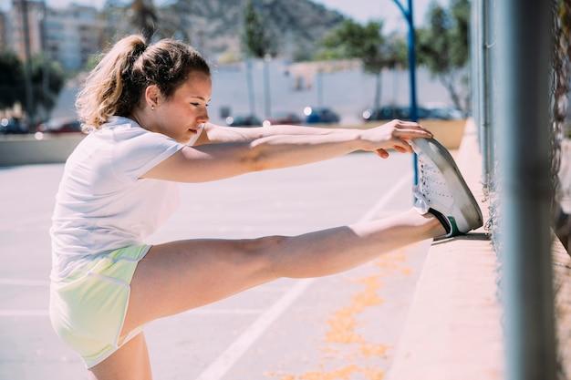 Flexibele jonge vrouw die zich uitstrekt been Gratis Foto