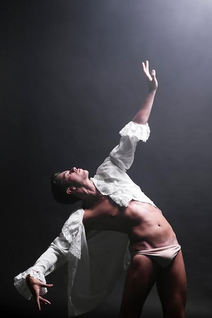Flexibele man strekt de hand uit om te gloeien Gratis Foto
