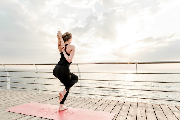 Flexibele vrouw die yogaasana dichtbij het overzees op zonsopgang in de ochtend doen Premium Foto