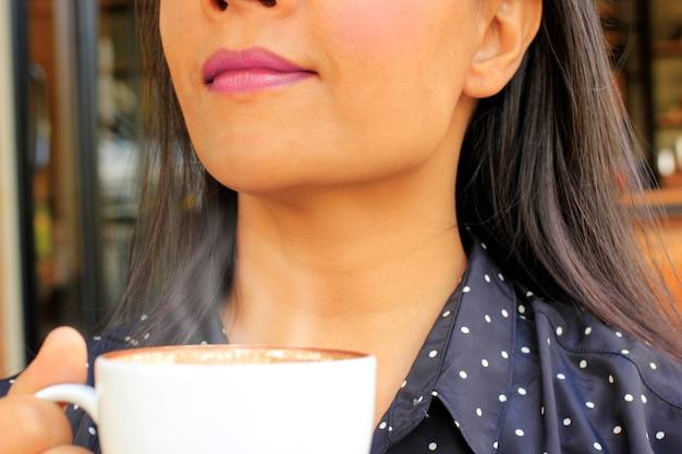 Focus op de lippen van een jonge vrouw die graag warme koffie drinkt. Premium Foto