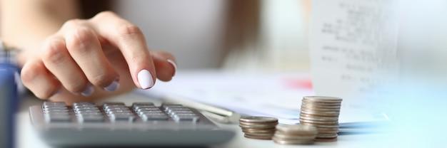 Focus op tedere handen van geestige zakenvrouw die binnenshuis zit en de rekenmachine gebruikt om te tellen in belangrijke tablet met grafieken. kantoor concept. onscherpe achtergrond Premium Foto