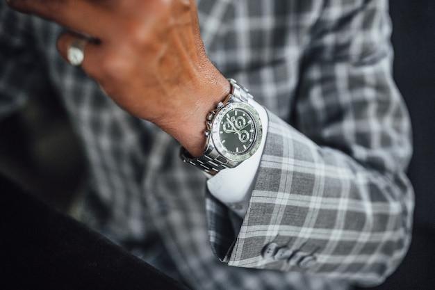 Focus op zeer dure watch.gray kleur pak, zwarte achtergrond, close-up Premium Foto