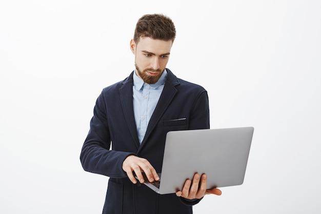 Focussen op zaken. portret van slimme en ambitieuze geconcentreerde knappe jonge mannelijke ondernemer met baard en blauwe ogen laptop in de hand houden bladeren controleren schema met vastberaden blik Gratis Foto