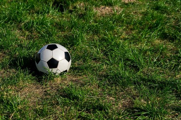 Fotball of voetbal zwart-witte bal op groene grasachtergrond. Premium Foto