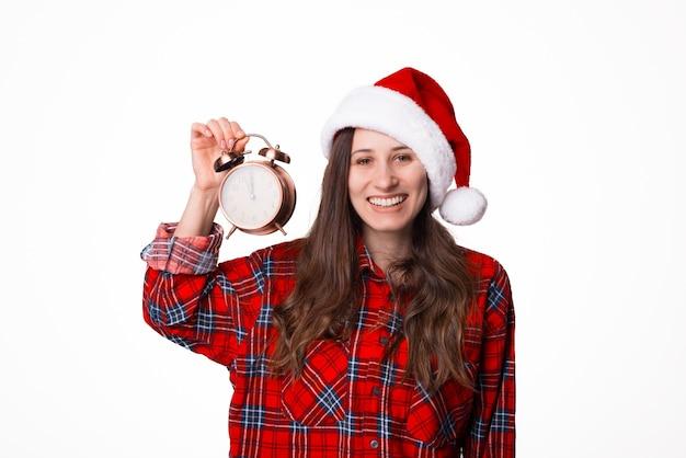 Foto die van jonge vrouw in kerstmissanta hoed en een uitstekende klok op witte achtergrond houdt Premium Foto