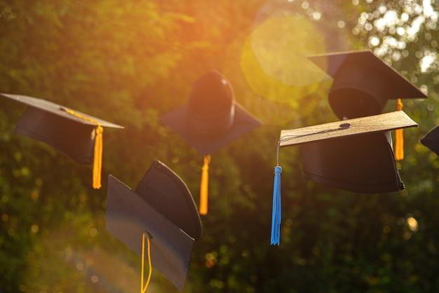 Foto's van de hoeden van afgestudeerden op de achtergrond zijn vage bokeh. Premium Foto