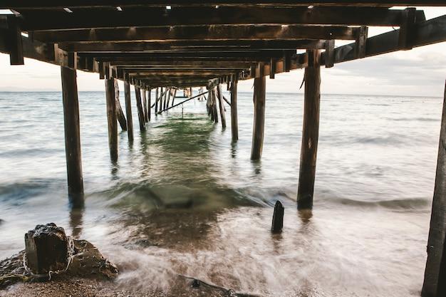 Foto's van onder de houten brug die zich uitstrekte naar de zee Premium Foto