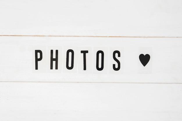 Foto'stekst en zwarte hartvorm op witte houten achtergrond Gratis Foto