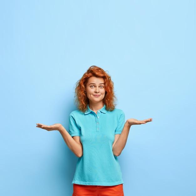 Foto van aantrekkelijk roodharige duizendjarige meisje heft handpalmen op, voelt twijfel, kan niet kiezen tussen twee items, draagt een casual blauw t-shirt, heeft kuiltjes in het gezicht, is onverschillig, voelt aarzeling. Gratis Foto