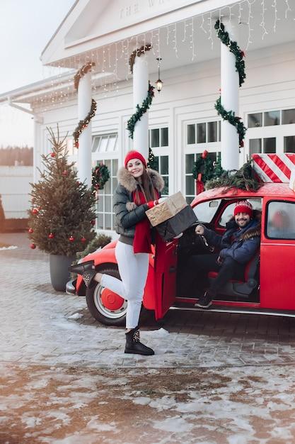 Foto van aantrekkelijke blanke vrouw in warme kleren draagt dozen met kerstcadeaus in een auto naar haar vriendje Gratis Foto