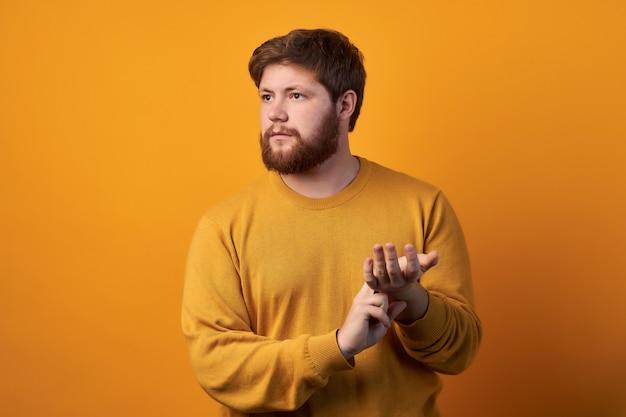 Foto van aantrekkelijke man draagt een ronde bril, houdt de hand op de pols, controleert pols of hartslag, zorgt voor zijn gezondheid, heeft hartkloppingen, modellen tegen witte achtergrond Premium Foto
