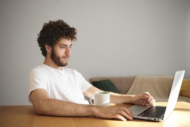 Foto van aantrekkelijke stijlvolle jongeman met wazige baard glimlachend series online kijken of surfen op internet met behulp van wifi op zijn generieke laptop, zittend aan een houten bureau met mok, koffie of thee drinken Gratis Foto