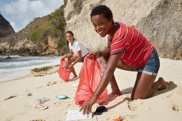 Foto van actieve verantwoordelijke vrijwilligers verzamelen zwerfvuil op zandstrand Gratis Foto