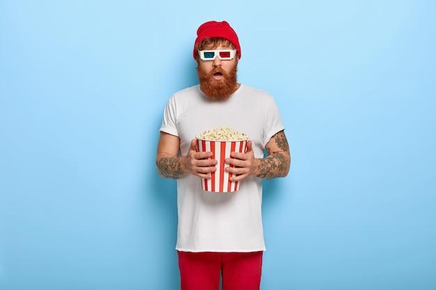 Foto van bang gember man kijkt naar nieuwe horrorfilm in de bioscoop, eet popcorn Gratis Foto
