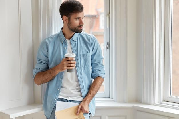 Foto van bebaarde administratieve mamager houdt papieren, wegwerp kopje koffie Gratis Foto