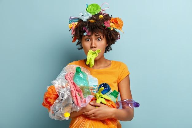 Foto van beschaamde jonge krullende afro-amerikaanse vrouw heeft rubberen handschoen in de mond, draagt plastic afval, maakt zich zorgen over wereldwijde milieuvervuiling, geïsoleerd op een blauwe muur. ecologie concept Gratis Foto