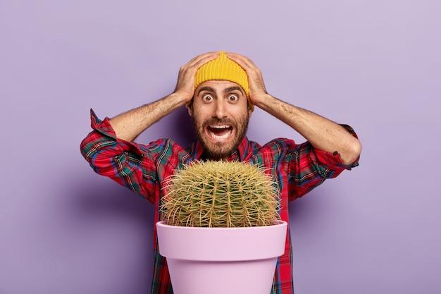 Foto van beschaamde verbijsterde blanke man houdt de handen op het hoofd, staart geschokt, gekleed in een geruit overhemd en een gele hoed, staat achter de pot met grote cactus, geïsoleerd op paarse achtergrond Gratis Foto