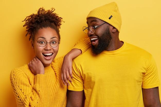 Foto van blij afro-meisje leunt op de schouder van vriendje, voelt zich gelukkig, sta dicht, positieve emoties uiten Gratis Foto