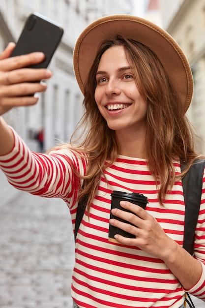 Foto van blije europese vrouw poseert voor het maken van selfie, geniet van wandeling in het centrum, recreëert buiten Gratis Foto