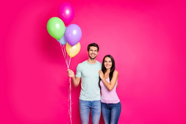 Foto van charmante man en dame paar lucht ballonnen in handen houden kwam naar ouders verjaardagsfeestje dragen casual outfit geïsoleerde roze kleur achtergrond Premium Foto
