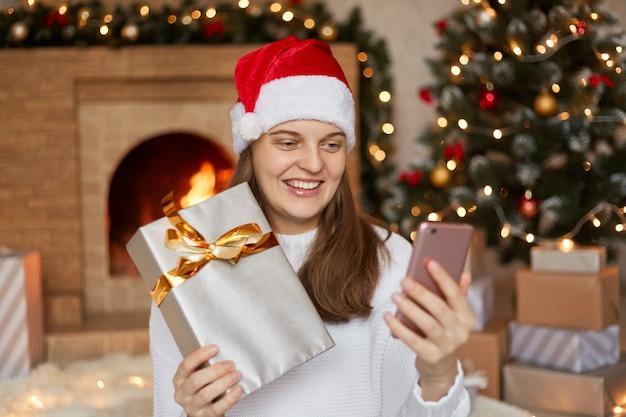 Foto van charmante schattig mooi aantrekkelijk meisje haar telefoon en geschenkdoos in handen houden Premium Foto