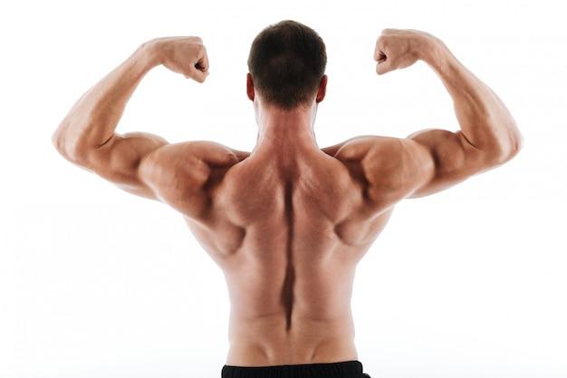 Foto van de atletische jonge mens die zijn rug en bicepsspieren toont Gratis Foto