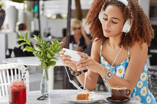 Foto van donkere vrouwelijke chats op mobiele telefoon, verbonden met draadloos internet in cafetaria, luistert favoriete liedje in afspeellijst met koptelefoon, geniet van koffie met cake Gratis Foto