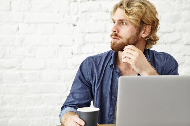 Foto van doordachte serieuze jonge europese man met dikke baard ontspannen in koffiehuis, genieten van ochtend cappuccino, zit open laptop tijdens het ontbijt en het lezen van nieuws Gratis Foto