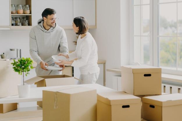 Foto van druk gezinspaar persoonlijke spullen uit kartonnen dozen uitpakken, gekleed in vrijetijdskleding, witte borden vasthouden, poseren in ruime keuken met modern meubilair, omgeven met stapel pakketten Premium Foto