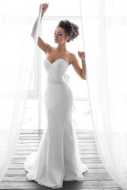 Foto van een bruid in een witte lange jurk met make-up en kapsel Premium Foto