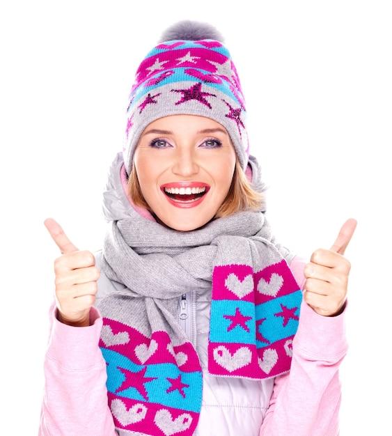 Foto van een gelukkig volwassen meisje in winterkleren met heldere positieve emoties toont duimen omhoog teken geïsoleerd op wit Gratis Foto