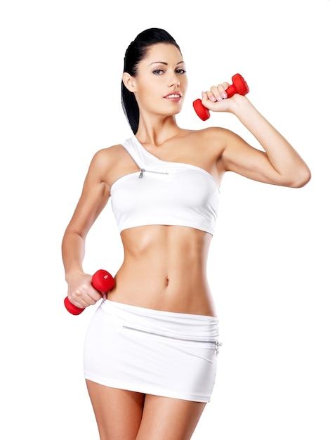 Foto van een gezonde opleiding jonge vrouw met halters. Gratis Foto