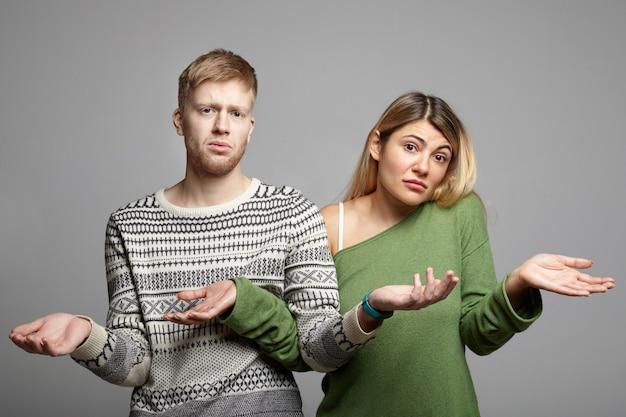 Foto van een grappig jong koppel, man en vrouw met twijfelachtige, clueless blikken, schouders ophalen met open handpalmen, zich verloren voelen, in verwarring en onzekerheid kijken. lichaamstaal Gratis Foto