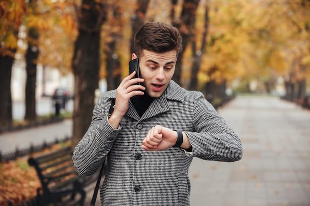 Foto van een jonge kerel die op smartmobile spreekt terwijl hij op zijn horloge kijkt en te laat is Gratis Foto
