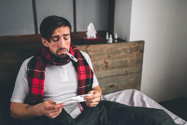 Foto van een jonge man met zakdoek. zieke man ligt in bed en heeft een loopneus. man maakt een remedie voor de verkoudheid. model man heeft een hoge temperatuur, hoofdpijn, migraine Premium Foto