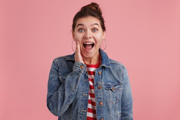 Foto van een jonge vrouw met sproeten, steekt een hand in het gezicht en wil je het schokkende nieuws vertellen, gekleed in een gestreept t-shirt van een spijkerjasje, kijkend naar de camera, geïsoleerd over een roze muur. Gratis Foto