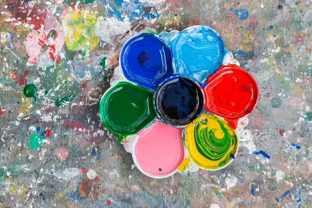 Foto van een kunstenaarspalet geladen met diverse kleurenverven op de houten lijstachtergrond Premium Foto