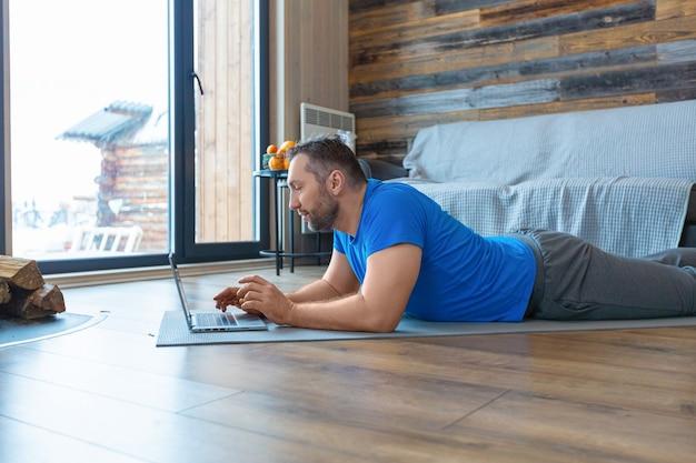 Foto van een man van middelbare leeftijd tijdens een online videogesprek. hij ligt op de grond terwijl hij voor een laptopmonitor staat. Premium Foto