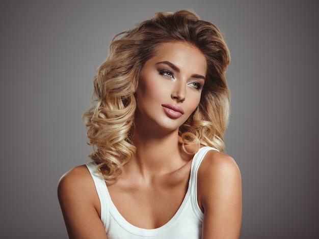 Foto van een mooi jong blond meisje met krullend haar. close-up aantrekkelijk sensueel gezicht van blanke vrouw met lang haar. smokey-oogmake-up. Gratis Foto