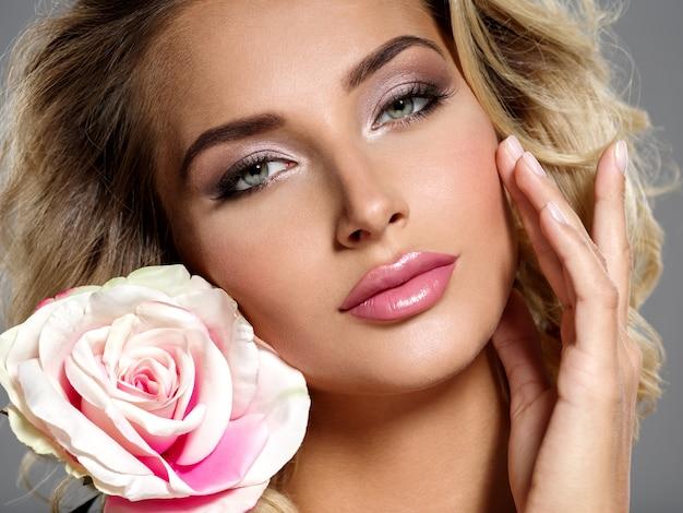 Foto van een mooie blonde vrouw met bloem. close-up aantrekkelijk sensueel gezicht van blanke vrouw met krullend haar. smokey-oogmake-up. Gratis Foto