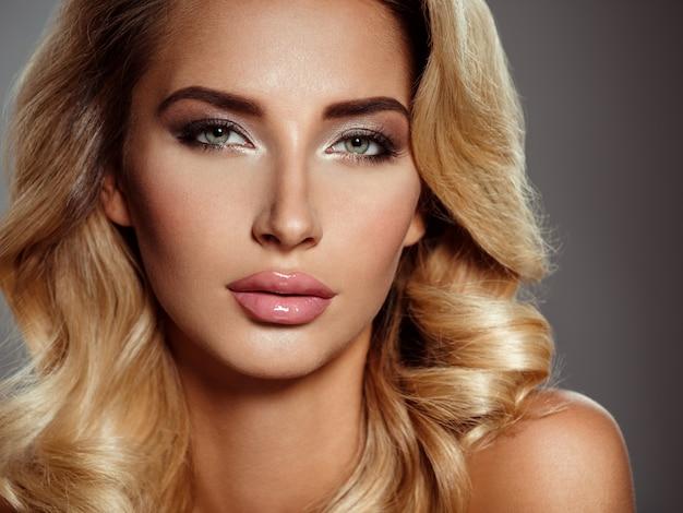 Foto van een mooie jonge blonde vrouw met krullend haar. close-up aantrekkelijk sensueel gezicht van blanke vrouw. smokey-oogmake-up. Gratis Foto