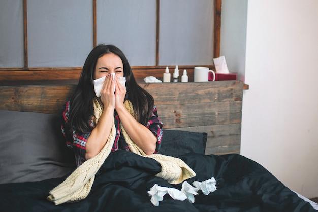 Foto van een mooie vrouw in het bed met zakdoek. ziek vrouwelijk model heeft loopneus. meisje maakt een remedie voor de verkoudheid Premium Foto