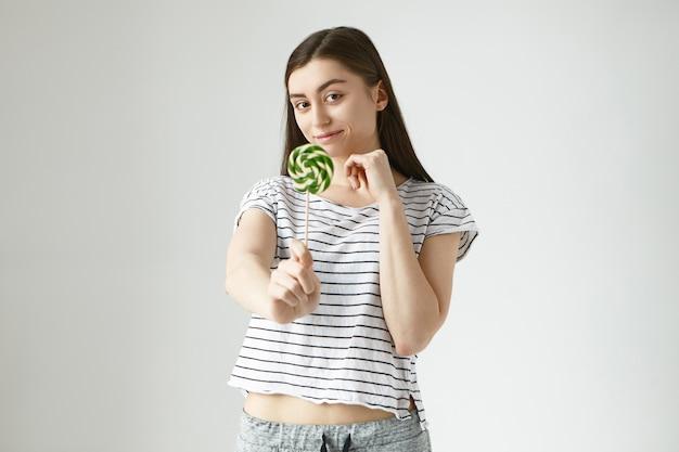 Foto van een positieve gelukkige 20-jarige vrouw met glanzend donker haar die hand reikt met spiraalvormig kleurrijk zoet hard snoepje, dat u aanbiedt om het te hebben. mensen, voedsel, voeding, dieet en snoepconcept Gratis Foto