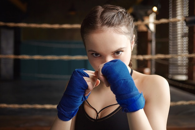 Foto van een stijlvolle 18-jarige vrouw bokser met sterke armen en een atletisch fit lichaam die binnenshuis traint en de boksvaardigheden en -technieken onder de knie krijgt Gratis Foto