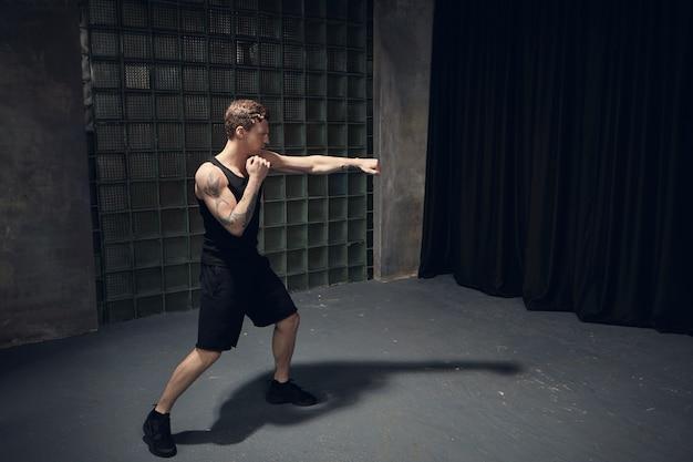 Foto van een stijlvolle fitte blanke man met gespierde getatoeëerde schouders boksen in een lege ruimte die een hand reikt, stoten onder de knie tijdens de voorbereiding op de strijd. mensen, gezonde levensstijl en sport Gratis Foto