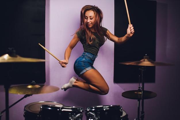 Foto van een vrouwelijke drummer die een drumstel speelt Premium Foto