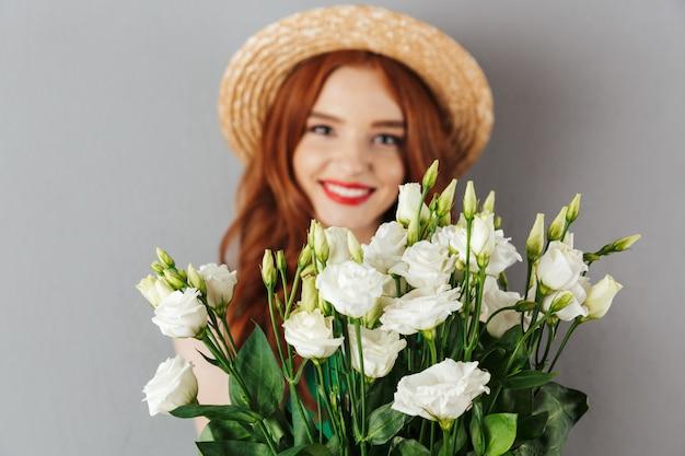 Foto van elegante vrouw jaren '20 met rood haar die strohoed dragen en bos van witte bloemeneustoma houden, die over grijze muur wordt geïsoleerd Premium Foto