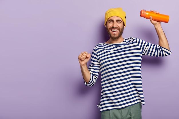 Foto van energieke vrolijke man toerist danst speels, gekleed in modieuze kleding, draagt thermoskan, glimlacht graag, heeft een gelukkig humeur, geïsoleerd op paarse achtergrond. Gratis Foto