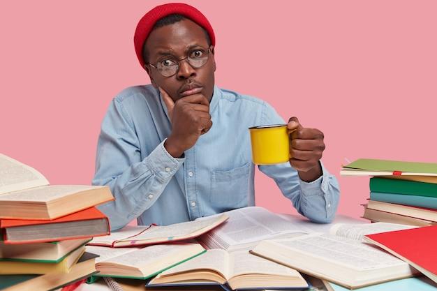 Foto van ernstige zwarte man houdt kin, draagt gele mok drank, kijkt rechtstreeks naar camera, draagt rode hoed en shirt Gratis Foto