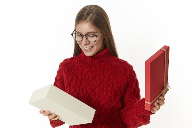 Foto van extatische mooie jonge vrouw met bril en gezellige trui geschenkdoos openen Gratis Foto